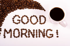 Good morning written in the coffee beans with a filled coffee cup Royalty Free Stock Photography