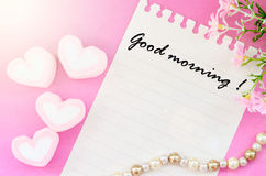 Good morning written. Good morning written with sweet heart shape of pink marshmallows with flower on pink background Royalty Free Stock Images