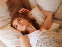Good Morning! Young beautiful woman waking up in her bed fully r Royalty Free Stock Photo