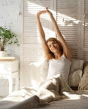 Good Morning! Young beautiful woman waking up in her bed fully r Royalty Free Stock Photography