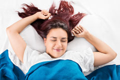 Good morning. Young girl waking up while stretching in bed in the morning Royalty Free Stock Photo