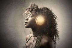 Good music. Attractive black woman listening to music royalty free stock photography
