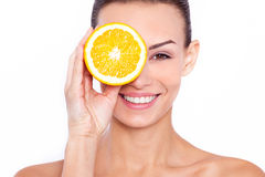 Good for my skin!. A young attractive woman holding an piece of orange and smiling at the camera Royalty Free Stock Image