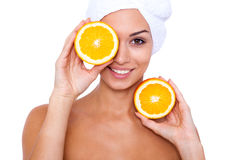 Good for my skin!. A young girl takes spa treatments with oranges in hand. White background Stock Photography
