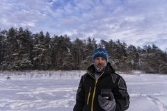 Good-natured bearded man with a snowy beard, slight smile and GPS navigator is standing on the edge of a taiga forest. Good-natured bearded man with a snowy royalty free stock photo