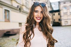 Good-natured girl with long curly hair and vinous lips is smiling to camera in the city.  royalty free stock photos
