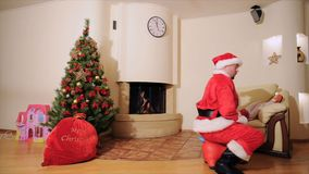 Good New Year spirit: Christmas tree, gift bag, fireplace - Dad and daughter play the fool. Santa jumping. Good New Year spirit: Christmas tree, gift bag stock footage