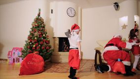 Good New Year spirit: Christmas tree, gift bag, fireplace - Dad and kids play the fool. Good New Year spirit: Christmas tree, gift bag, fireplace - Dad and stock video footage