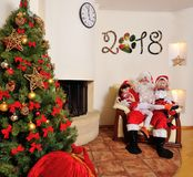 Good New Year spirit: Christmas tree, gift bag, fireplace and decoration. Santa and two kids Stock Image