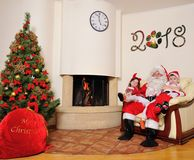 Good New Year spirit: Christmas tree, gift bag, fireplace and decoration. Santa and two kids Royalty Free Stock Photo