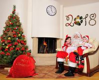 Good New Year spirit: Christmas tree, gift bag, fireplace and decoration. Santa and two kids royalty free stock images