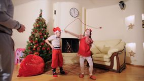 Good New Year spirit: Christmas tree, gift bag, fireplace - kids play the fool, they are cozy and homey waiting for Santa. Good New Year spirit: Christmas tree stock video
