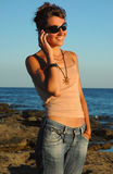 Good news!. Young attractive woman talking with mobile phone, standing near the sea Royalty Free Stock Image