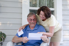 Good News. A middle aged couple reads a letter on the porch of their vintage house, enjoying reading good news together Stock Image