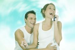 Good news. Young couple laugh over a funny phone discussion stock photo