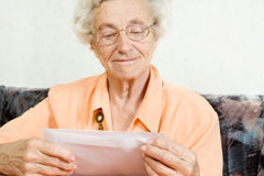 Good news. A elderly woman is opening a envelope Royalty Free Stock Image