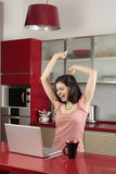 Good news. Young woman with laptop in the kitchen receiving good news Stock Photography