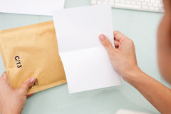 Good news. Bad news. Woman reading letter. Blank card and envelope over grey background Stock Images