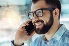 Funny bespectacled man having phone conversation and smiling. Good news. Beardful funny bespectacled man keeping cellphone near his head having phone Royalty Free Stock Photography