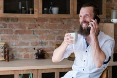 Good news business communication man smartphone. Good news at breakfast. Communication. Happy young man talking business. Latte cup and smartphone in hands stock image
