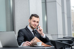 Good news. Confident businessman talking on the phone and drinki Stock Images