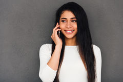 Good news from friend. Attractive young African woman talking on mobile phone and smiling while standing against grey background Royalty Free Stock Photos