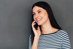 Good news from friend. Attractive young woman talking on the mobile phone and smiling while standing against grey background Royalty Free Stock Photos