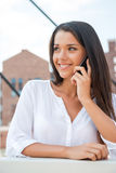 Good news from friend. Beautiful young woman talking on the mobile phone and smiling while standing outdoors Stock Photography