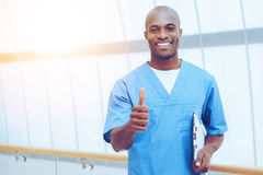 Good news!. Happy young African doctor in blue uniform holding clipboard and showing his thumb up Stock Image