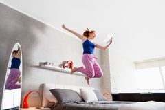 Good News For Happy Young Woman Girl Jumping On Bed Royalty Free Stock Photography