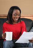Good news letter. African american woman all smiles reading a letter with good news Royalty Free Stock Photos
