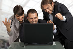 Good news in the office. Three businesspeople gesturing and smiling over a laptop stock photos