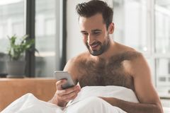 Cheerful guy messaging on mobile phone in morning. Good news. Portrait of happy young man using smartphone at home. He is sitting on bed after sleeping and Stock Photography