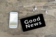 Good News on tablet pc screen with smart phone. Stock Images
