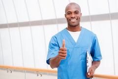 Good news for you!. Happy young African doctor in blue uniform holding clipboard and showing his thumb up Royalty Free Stock Image