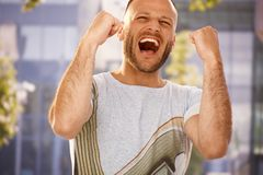 Good news. Young man shouting with hapiness outdoors, clenching fists Royalty Free Stock Image