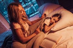 Mom and daughter at home. Good night, princess! Attractive young women with little cute girl are spending time together at home. Mom is putting daughter to bed Royalty Free Stock Photo