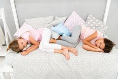 Good night and sweet dreams. Girls fall asleep after pajamas party in bedroom. Girls have healthy sleep. Children relax. On bed. Sleepy kids in pajamas having royalty free stock images