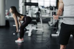 Good picture of boy and girl working out with dumbells in jym stock image
