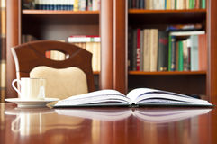 Good place for reading. Table, book, coffee and bookshelves Stock Images