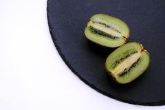 Chopped kiwi on black shale. Good quality close up photo of a chopped in a half kiwi on some black shale plate with round edges, view from the top. The main Royalty Free Stock Photos