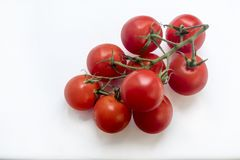 Branch of fresh cherry tomatoes. Good quality close up photo of fresh ripe cherry tomatoes on green branch served on some pure white surface, so you may easily stock photography