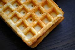 Viennese waffles on wood. Good quality close up photo of typical Viennese waffles, served on some dark oak wooden plate. This wafers usually looks like cell royalty free stock photos