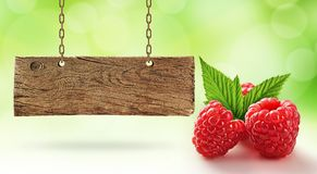 Fresh raspberry and wooden board. Good quality and fresh raspberry and old, wooden signboard Royalty Free Stock Photo