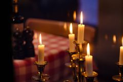 Candles, romantic evening, restaurant. Good quality picture of a few decorative candles, burning in the darkness, some candles in a candlestick are in focus stock image