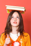 Good read. Girl with books on her head holding thumb up Stock Photo