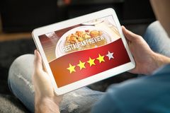 Good restaurant review. Satisfied and happy customer. Good restaurant review. Satisfied and happy customer giving great rating with tablet on an imaginary Royalty Free Stock Photo