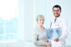 Good results. Senior patient and radiologist with x-ray looking at camera in hospital Royalty Free Stock Image