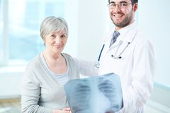 Good results. Senior patient and radiologist with x-ray looking at camera in hospital Stock Photography