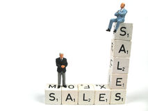 Good sales and bad sales. Two businessman standing and sitting on the word sales stock photos